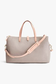 Our favorite travel bag gets an update in canvas. This spacious beauty features multiple pockets, a removable crossbody strap and metal feet for added protection. Travel Handbags, Travel Bags, Navy Tote Bags, Fab Bag, Travel Accessories, Italian Leather, Pebbled Leather, Purses And Bags, Zipper