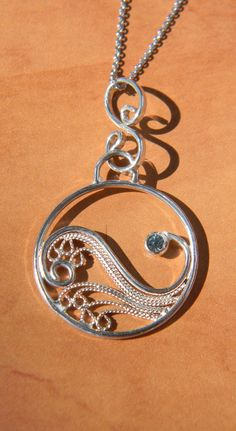 This handmade sterling silver filigree pendant is reminiscent of ocean waves or a yin yang symbol. The filigree work is an open lattice