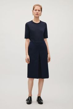 Designed with a chunky front pleat, this skirt is made from a pure cotton with a twill texture wool. An A-line shape and fit, it has simple in-seam pockets, a comfortable elastic waist and a hidden zip at the back.