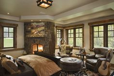 Rustic Traditional Bedroom Ideas with Fireplace and Sitting Area Picture - I love the big windows and the stone fireplace!