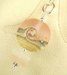 Ultra-rare pinks sea glass gem found in Northern California Recently. What a find ! It probably began as a piece of Depression Glass. Really, really special ! A beautiful piece of white sea glass adds to the pendant. The glass bead depicts a beautiful starry night with a wave cresting in the ocean.Gold star are sprinkled across the sky. It is hard to capture how detailed and beautiful this bead is without seeing it in person. It is magnificent!. I wire-wrapped the sea glass and bead...