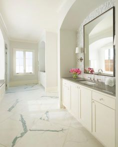Arched cutouts frame the vanity set up in this bright bathroom. Vertical backsplash tile adds subtle texture and shading behind a large mirror. Gray countertop compliments the gray marbling on the floor tile. The fixtures are built in on each wall leaving open floor space to move through the center of the room.