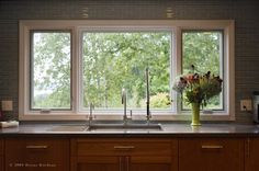 Kitchens are great rooms for variations on Chicago windows, ones that are shorter but also impressive in terms of views. Here one can enjoy the trees and water beyond while washing the dishes.