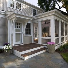 "Back Entry. Large steps and landing are welcoming and easy to navigate. Dark porch floor ads contrast. Screened in porch with separate entry gives ""peek"" into home and gives relaxed appearance. Potted flowers are easier to manage. Shade trees and door awning. Multi sized stone/paver patio ads texture and greys and blues. Clean bracket and molding detail are ornate but not fussy."