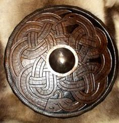 One Viking Iron Boss in a Viking Round Shield of Encircling Leather. At the centre of the Viking shield's was a circular hole covered by a more-or-less hemispherical iron boss of ~15 cm diameter (including flange), which enclosed the hand grip. The iron of the dome was fairly thick (3-5 mm), though the flange was somewhat thinner. Tough stuff!