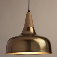 Crafted with an open teardrop silhouette, our exclusive pendant light boasts a mid-century modern design with a burnished brass shade flowing from a natural wood tip. Hang several in a row for an inspiring lighting solution with a clean, symmetrical look.