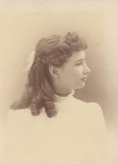 Circa 1890 portrait of Helen Keller as a young girl in profile with curled hair pulled back with a white bow, taken while she was a student at the Perkins School for the Blind.