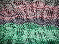 Волнистый ажурный узор спицами с вытянутыми петлями.