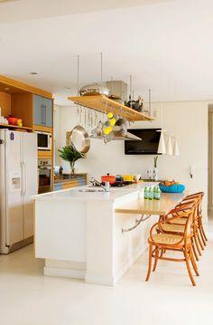 bancada colada na ilha central. A mesa serve de apoio para refeições rápidas e para quem assiste ao preparo dos pratos. Mesa e armários da Kitchens foram revestidos de laminado da Formica.