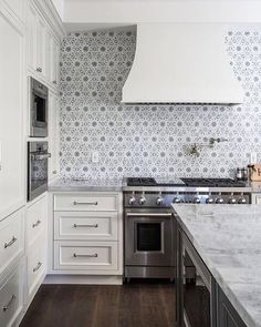 This backsplash! Ivory and gray kitchen features ivory shaker cabinets paired with marble countertops and a gray flower mosaic tiled backsplash, Walker Zanger Villa d'oro Collection Granada Decorative Field in Grigio. Ivory Kitchen Cabinets, Kitchen Tile, Kitchen And Bath, New Kitchen, Shaker Cabinets, White Cabinets, Kitchen Ideas, Wall Cabinets, Layout Design