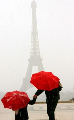 Red umbrellas at the Eiffel Tower during a hail storm. Photo by Owen Franken
