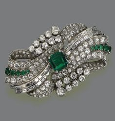 EMERALD AND DIAMOND BROOCH, CIRCA 1935, The plaque designed as a stylized bow-knot, set in the center with an emerald-cut emerald weighing approximately 4.75 carats, completed by 122 old European-cut and single-cut diamonds and 38 baguettes weighing approximately 16.75 carats.