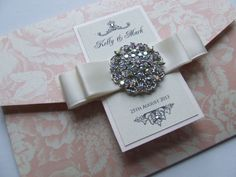 Vintage wedding invitation with brooch and satin ribbone from Wedding Paraphernalia