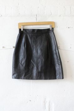 A basic that is not so basic. Vintage flared high waist mini skirt in smooth black leather with a snap tab detail in back, snap/zip closure and satin lining. Easy peezy! Label: None Size: Small Conten