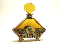 Hoffman Jeweled Egyptian Perfume.  1920s Hoffman perfume bottle and stopper in amber crystal, in Egyptian style enamel and jeweled metalwork, matching front and back, dauber. 7 in. Photo & description by Perfume Bottles Auction