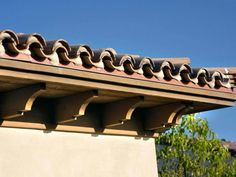 The closed-beam eaves supported by wood outriggers, along with the mudded texturing of the S-tiles, reinforce the architectural details.