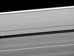 Pan rides the 200 mile wide Encke gap and casts a shadow.  Cassini