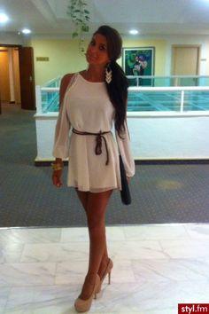 Vestido blanco de media manda con un cinturón negro con un lazo en el cinturón, los hombros descubiertos y tacones color maquillaje