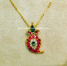 Simple paisley design gold pendant studded with precious rosecut rubies, emeralds and uncut diamonds. The mango design ruby pendant dns Gold Pendent, Ruby Pendant, Pendant Set, Gold Earrings Designs, Gold Jewellery Design, Gold Jewelry, India Jewelry, Temple Jewellery, Gold Necklace Simple