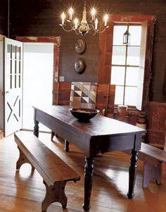 FARMHOUSE – INTERIOR – vintage early american farmhouse showcases raised panel walls, barn wood floor, exposed beamed ceiling, and a simple style for moulding and trim, like in this farmhouse with traces of blue paint on a late-1800s table complement the dining room's walls.