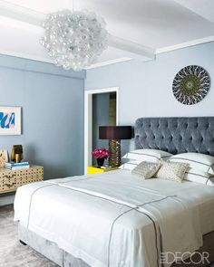 A Ryan McGinness print in the master bedroom hangs above a headboard upholstered in a  Lelièvre velvet; the Venetian light fixture is from the 1930s, the bedside lamp is by Hervé Van  der Straeten, and the walls are covered in a Holland & Sherry fabric.   - ELLEDecor.com