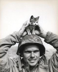 "Iwo Jima , March 1945: The caption reads ""Corporal Edward Burckhardt, of Yonkers, New York, sports a kitten that he found at the base of Suribachi Yama on the battlefield at Iwo Jima when he came ashore with the 5th Marine Division.""    From the Holland Smith Collection (COLL/2949) at the Marine Corps Archives and Special Collections"