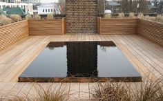 reflective dark pool, wood roof deck, corten frame, water jets. night lighting, designed by Bamber Wallis