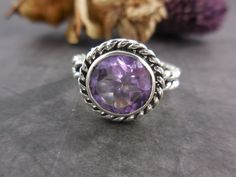 Made with 10mm round faceted amethyst quartz gemstone and sterling silver bezel and wire. Size 8.0