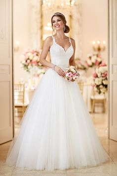 Two Stella York dresses in one! This above-knee lace dress features a removable floor-length tulle and Royal organza princess skirt. The back of the dress features beaded illusion lace that zips up with ease under coordinating pearl buttons. Style 6223 by @stellayorkbride. See more Stella York gowns on @weddingwire!