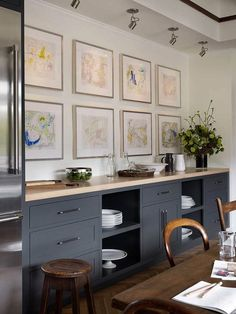 Gray kitchen cabinets with cream counters, herringbone wood floors and art gallery wall.