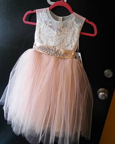 A stunning yet unique flower girl dress perfect for any wedding or special occasion. This tea length beauty is made out of sheer netting, French lace , champagne blush tulle and sash. Our current turn around time is 8 weeks plus shipping time.  Please take note our current turn around time is 8 weeks plus shipping time which usually takes additional 3 - 5 business days.  SIZE CHART  Please take note these measurements reflect childs body measurement not garment, finished garment will be…