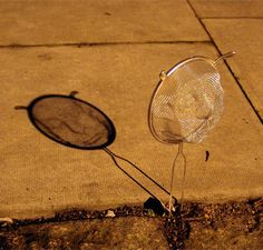 Shadow Faces installation by Isaac Cordal | Isaac Cordal created three-dimensional grid faces and used street lights to cast their shadows onto the pavement in London, England. 3D faces were sculpted into the metal grids of several kitchen strainers. |