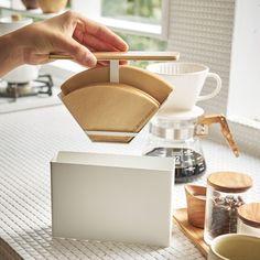 フタを引き上げるだけ。温もりある木目と白の組み合わせ上品なコーヒーペーパーフィルターケース。「コーヒーペーパーフィルター ホルダー トスカ」のご紹介です。収納場所に困るコーヒーペーパーフィルターをスマートに収納できるケースです。フタの裏ににフィルターをセットする構造になっているので、フタを引き上げるだけでフィルターを取り出すことができます。本体に収納すればほこりやゴミが付きから守ることができ、衛生的にお使いいただけます。ホルダーは真ん中に仕切りがあるので1~2杯用、3~4杯用と分けて収納する事ができます。ホルダーの底の穴にフィルターを差し込むので円すい型にも対応◎北欧風のデザインで、ダイニングテーブルや、キッチンカウンターなどに出しっぱなしでも気にならないので見せる収納にもピッタリです。■SIZE 約W18.5×D5.7×H14cm ■収納可能数 扇形:1~2・2~4杯用ペーパーフィルター約100枚(片方 約50枚) 円錐形:1~2・2~4杯用ペーパーフィルター約60枚(片方…