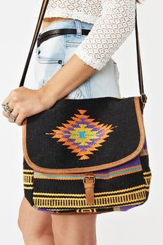 Awesome black woven satchel featuring a foldover flap with leather buckled detailing and a bright stripe print. Adjustable crossbody strap, fully lined interior with side pocket. Looks rad paired with a crop tank and high-waist cutoffs! By 7 Chi.