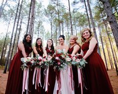 Bridesmaids and bride's bouquets, blush and burgundy with long, trailing ribbons. By Flaura Botanica.