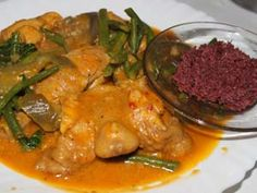KARE KARE MANOK = (CHICKEN KARE-KARE) = Ingredients : 1 Tbsp. anato seed 4 tsp. ginger, cut into strips 1 kilo chicken, cut into serving pieces 1 red onion, sliced 1 head garlic, crushed 1 cup peanut butter or Mama Sita's Kare kare mix 200 grams tomato sauce 4 pcs. medium size eggplants 2 cups evaporated milk or coconut milk 1 bundle pechay 1 cup stringbeans, cut 2 inches 1/2 cup cooking oil Bagoong alamang (Shrimp paste) ====