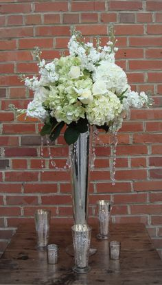 Tall Arrangement: white hydrangea, stock, roses, antique green hydrangea, ...in mercury glass vase with hanging crystals