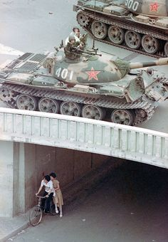 A Chinese couple on a bicycle take cover beneath an underpass as tanks deploy overhead in eastern Beijing, on June 5, 1989. (AP Photo/Liu Heung Shing)