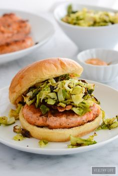 These Spicy Salmon Burgers topped with a roasted brussels sprout slaw will become your new favorite way to enjoy salmon. Salty and Crunchy these low-calorie, high protein burgers make the perfect healthy choice for the family.  Since they take only 20 minutes to prep and serve they are perfect for a weeknight dinner.  I topped my burgers with a simple roasted brussels sprout slaw to add a bonus superfood alternative. - A Healthy Life For Me