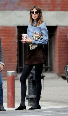 Alexa Chung looking rad in cat-eye retro sunglasses, a suede skirt, and tights.