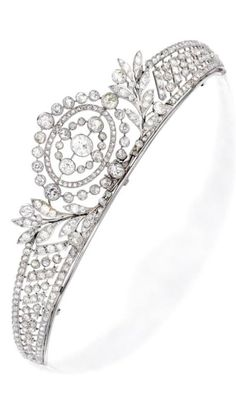 Platinum and Diamond Tiara. Of garland design centring an old European-cut diamond, accented by numerous old mine, old European, single and rose-cut diamonds, circa 1910; frame detachable. Accompanied by a black satin ribbon for affixing to the coiffure, the clasp set with three rose-cut diamonds; also accompanied by a later-added 14 karat white gold chain for wear as a necklace. #Edwardian #tiara