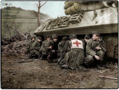 US 4th Infantry Div. troopers and German POWs. take cover from crossfire beneath an M10 tank buster somewhere in Germany, early 1945