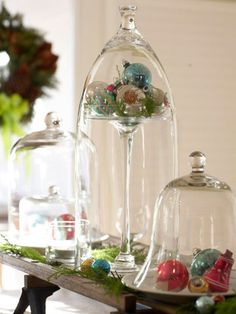Jingling Bell Jars  This tall centerpiece becomes the focal point of the table. Fill silver platters and cake stands with bright ornaments and cover with bell jars for holiday decor.