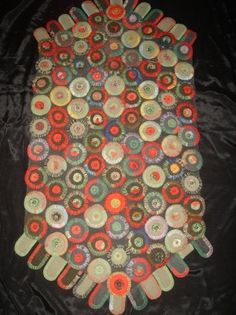 Early 20th.century.Wool pennies and peddles grey,black and red on a black cotton background.48in.by 24in.(120 cm by 19cm.). from antiques.com website