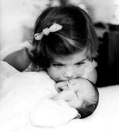 Caroline Kennedy kisses her new baby brother, John F. Kennedy, Jr. (known as John-John)