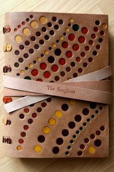 """The inspiration for the design came from using the idea of the """"spot and dot"""" paintings of the Aborigines, which tell a story about journeys. I had some naturally tanned split hide with a slightly rough surface which was perfect for the sand , and the spots were inlaid from lots of different leather scraps in various sizes and colours, but I tried to use natural colours"""