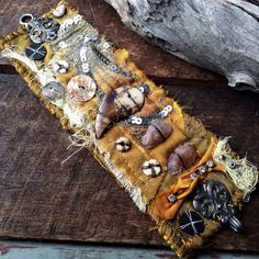 A gloriously shabby and tattered textile rustic tribal cuff in golden yellow hues. Recycled sari silk embellished with a carved bone claw, raw sunstone,