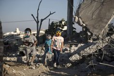 Palestinian children in Gaza City play in the rubble of buildings