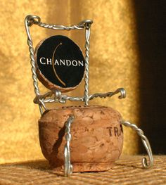 Graham Quinn crafted an interesting design using the whole cork, cap and wire from only one champagne bottle. It's neat that you can see the name on the cap and it becomes part of the design.