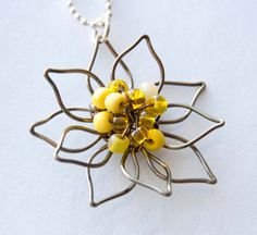 This unique and stunning flower is hand shaped with colored wire and glass beads. The flower is 1 1/2 in diameter. I often get compliments when